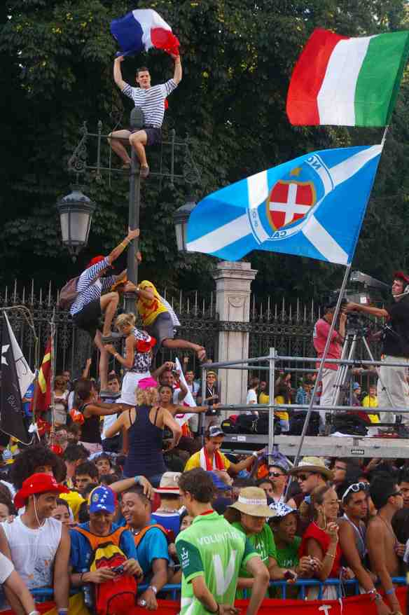 These French pilgrims climb a pole to get a better view of Pope Benedict passing in the Popemobile in the streets of Madrid.