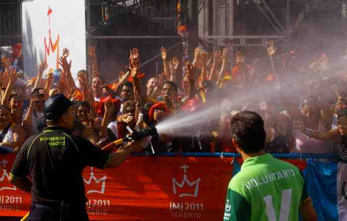 A fireman sprays the crowd to help pilgrims beat the heat.